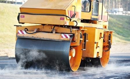 road paving: compactador de rodillo en el asfaltado de trabajo Foto de archivo