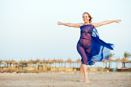 Happy woman with open arms on sea beach photo