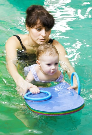 little girl and mothe in swimming pool photo