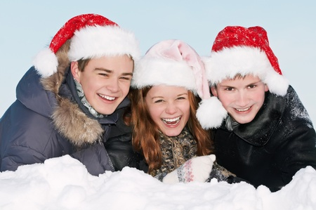 snowdrift: happy smiling young people lying in snowdrift