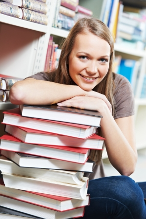 Young pretty smiling woman in a library with books at self-education photo