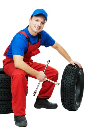 tire fitting: serviceman repairman automobile mechanic with car tire and spanner wrench isolated