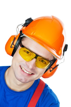 foremaster: close-up Portrait of young builder in protective safety equipment goggles hard hat earmuffs isolated