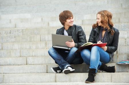 야외에서 컴퓨터 노트북과 함께 공부하는 두 학생