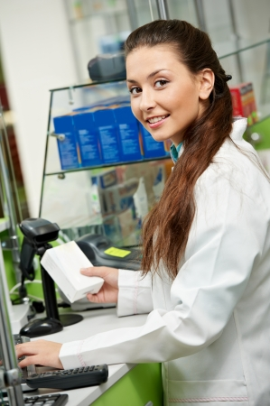 Young happy smiling pharmacist chemist woman working in pharmacy drugstore Stock Photo - 21717268