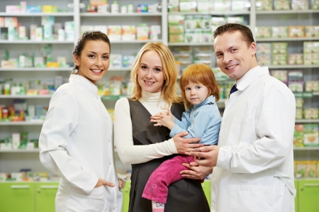 Cheerful pharmacist chemist woman giving vitamins to child girl in pharmacy drugstore Stock Photo