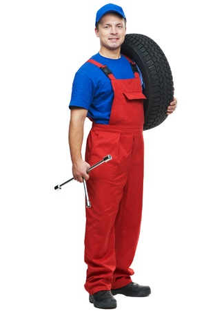 mechanician: serviceman repairman automobile mechanic with car tire and spanner wrench isolated