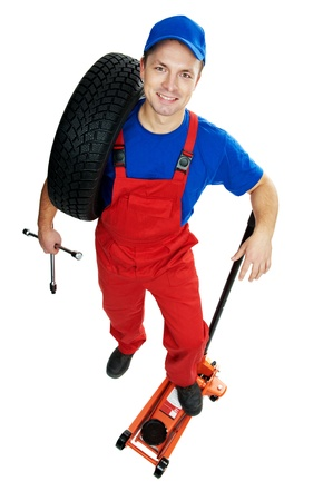 tire fitting: serviceman repairman automobile mechanic with car tire and lifting jack isolated