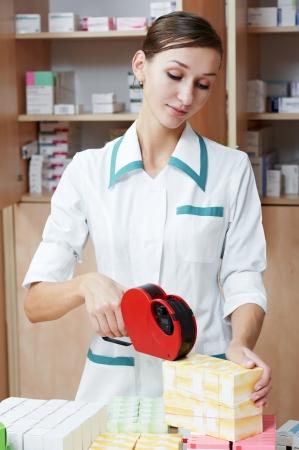 Pharmacistchemist marking drugs in pharmacy or drugstore
