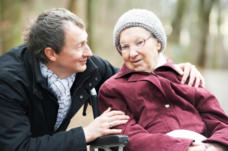 care home: old senior woman in wheelchair with careful son