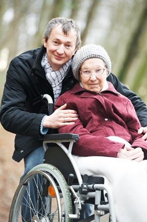 mobility nursing: old senior woman in wheelchair with careful son