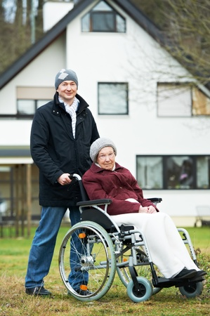 pensioner: old senior woman in wheelchair with careful son