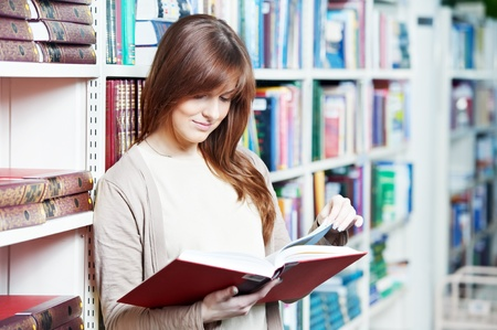 secondary education: young student girl reading book in library