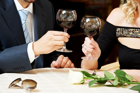 Man and girl hands with wine at cafe on a date photo