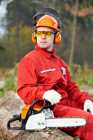 tree cutting: Lumberjack Worker With Chainsaw In The Forest Stock Photo