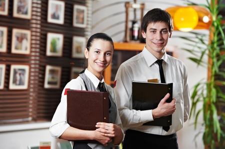 Waitress girl and waiter man in restaurant Imagens