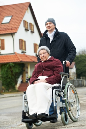 eldercare: old senior woman in wheelchair with careful son