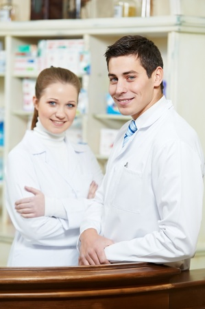 Two Pharmacy chemist workers in drugstore Stock Photo - 12589358