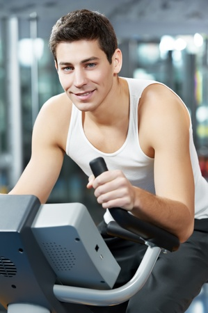 positive man at legs bicycle exercises machine photo