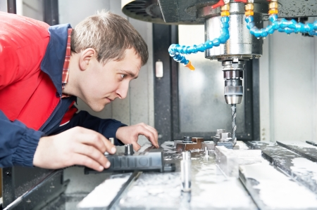 worker operating CNC machine center photo