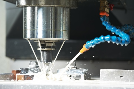 cutters: milling the metal blank with coolant Stock Photo