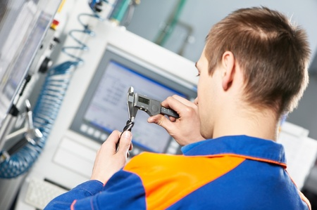 grinding: worker measuring detail tool Stock Photo