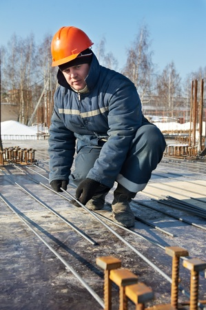 erector: builder works with concrete reinforcement Stock Photo
