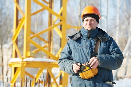 building worker: Builder with tower crane remote control equipment