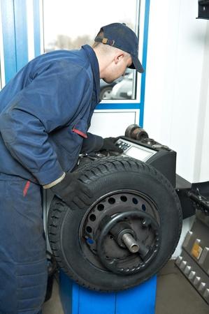 wheel balancing: machanic repairman at tyre balancing adjustment