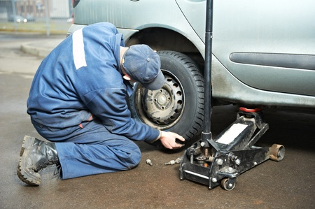 machanic repairman at tyre fitting with car jack Stock Photo - 12589739