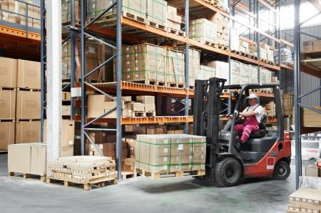 stockpiling: controlador de los trabajadores en el almac�n cargador de carretilla elevadora funciona Foto de archivo