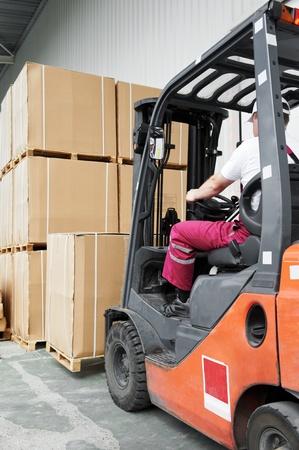 carretillas almacen: controlador de los trabajadores en el almacén cargador de carretilla elevadora funciona Foto de archivo