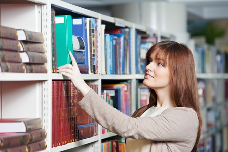 secondary education: young adult student selecting book in library