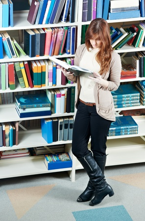 teenage girl happy: young student girl reading book in library