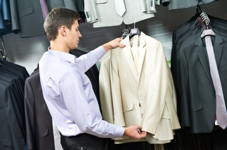 Young man choosing suit in clothes store photo