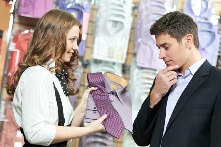 vendeurs: l'homme et assistant � l'habillement des v�tements achats