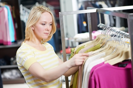 Young woman at clothes shopping store photo