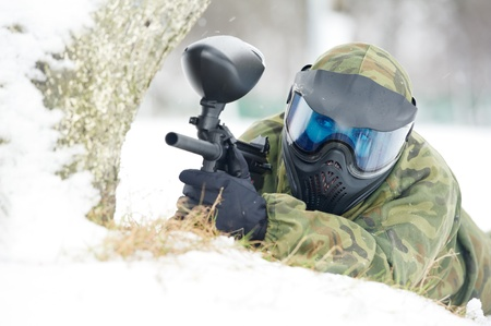 paintball player with marker at winter outdoors photo
