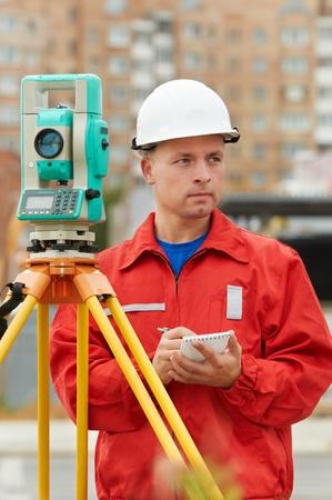 surveyor works with theodolite photo