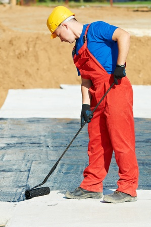 damp proofing: builder worker at roof insulation work