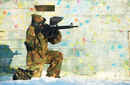 paintball: paintball player with marker at winter outdoors