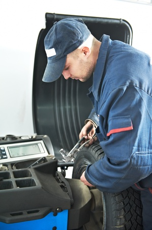 machanic repairman at tyre balancing adjustment photo