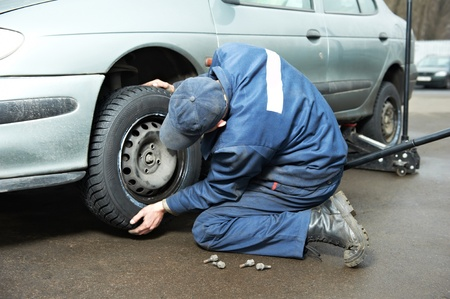 tight fitting: machanic repairman at tyre fitting with car jack