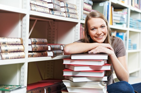 Smiling young adult woman reading  book in library photo