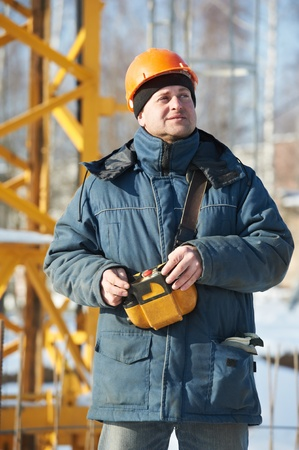 skilled: Builder with tower crane remote control equipment