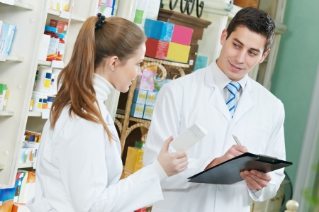 Two Pharmacy chemist workers in drugstore Stock Photo - 12872813