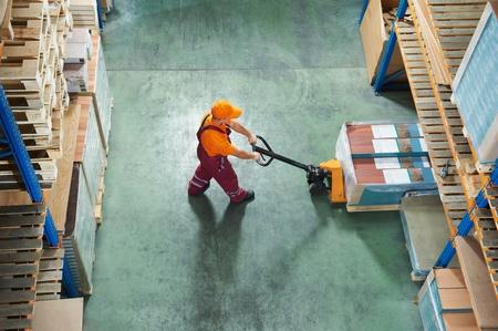 carretillas almacen: trabajador con camiones plataforma tenedor Foto de archivo