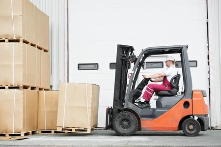 forklift truck: worker driver at warehouse forklift loader works