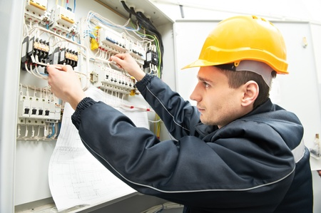 Electrician with drawing at power line box photo