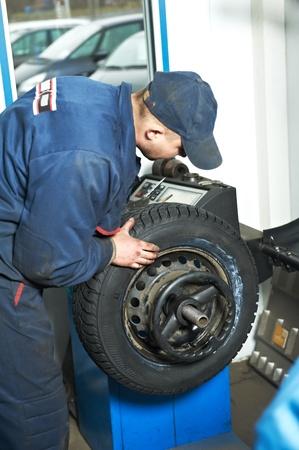 tire fitting: machanic repairman at tyre balancing adjustment
